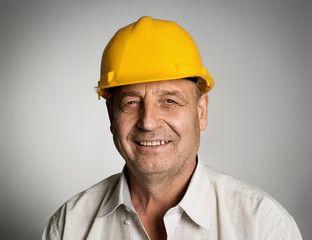 Smiling mature engineer or builder in yellow hardhat