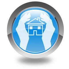 maison protégée entre deux mains sur bouton