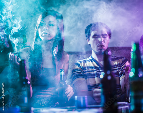 teens smoking marijuana in smoke filled room - 70671083