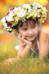 Little girl in autumn wreath of flowers lying on the grass