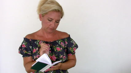Woman thinking while writing on a notepad