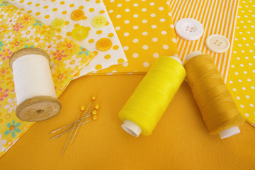 Accessories for sewing: threads, fabric, buttons in yellow-white