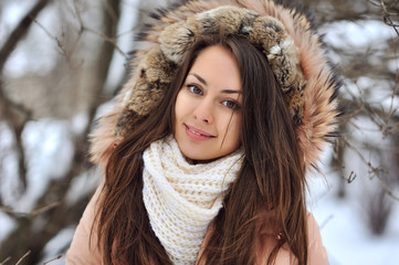 Beautiful winter portrait of young woman in the winter snowy sce