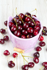 cherries in a bucket on wooden table
