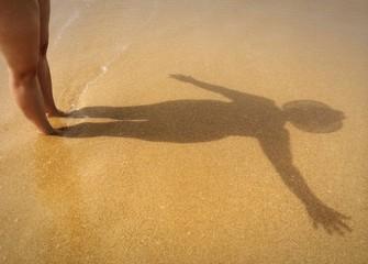 Frau am Strand winkt zum Meer hinaus