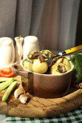 Young boiled potatoes in pan with vegetables on table in