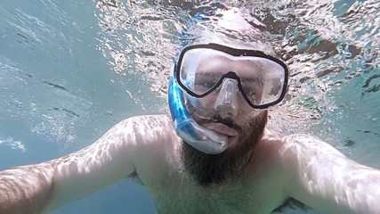 POV man snorkeling on surface of clear sea