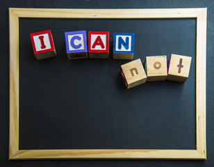 Wooden word I can not on blackboard