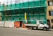 Leinwanddruck Bild - Cantiere edilizio palazzo, ponteggi sicurezza, autocarro