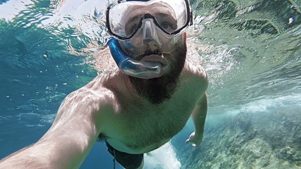Man snorkeling POV in clear water on surface of ocean