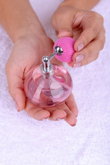 Woman hands holding perfume close up