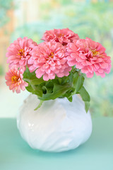 fresh pink flowers  in a ceramic vase on a blue background