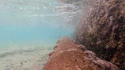 Rusty pipe just under ocean surface