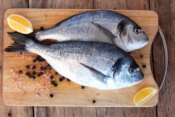 Two fresh gilt-head bream fish on cutting board