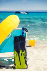 Beach accessories and chair on beach.  Summer vacation concept.