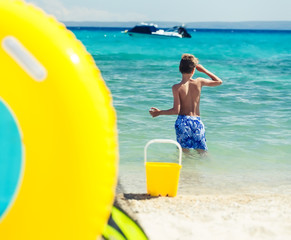 Child playing on beach with toys.  Summer vacation concept.