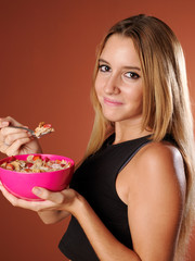 Young woman eating cereal with milk.