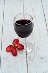 Glas rode wijn met druiven.