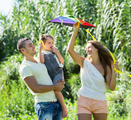 parents with little daughter and colorful kite