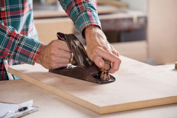 Carpenter's Hand Using Plane On Wood