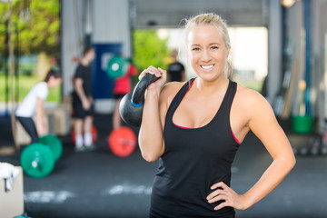 Happy Female Athlete Lifting Kettlebell