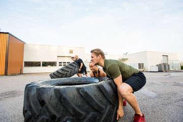 Fit Athletes Doing Tire-Flip Exercise