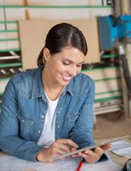 Female Carpenter Using Digital Tablet At Table