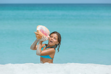 Funny girl sitting on the beach holding seashell and singing