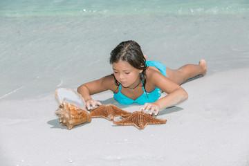 Little girl lying on white sand beach of Atlantic ocean