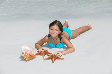 Joyful happy little girl lying on white sand beach