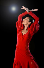 young Spanish woman dancing flamenco in typical folk red dress