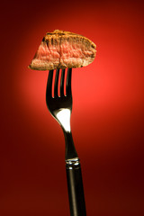 Piece of a grilled steak on a fork isolated on red