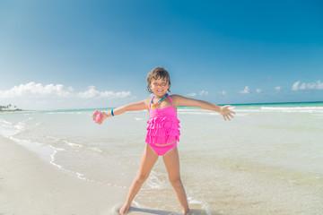 happy joyful smiling  little girl standing on the beach