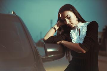 brunet near car at sunset street