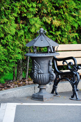 Wrought urn in a park near the bench. Ashcan