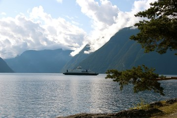 Mountains and fjord with a ferry in Norway.