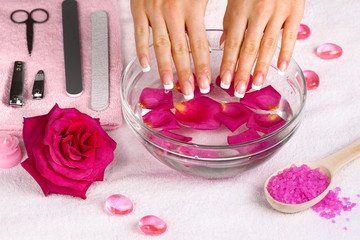 Beautiful woman's hands with french manicure in bowl of water