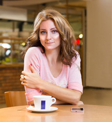 beautiful girl sitting in cafe and drinking coffee