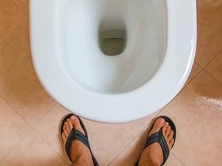 man's flip-flops feet in front of water closet