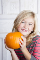 child holding small pumpkin up by her face