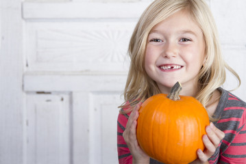 child holding a small pumpkin