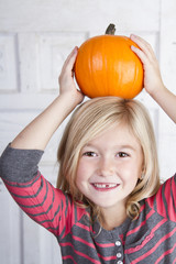 child holding small pumpkin on her head