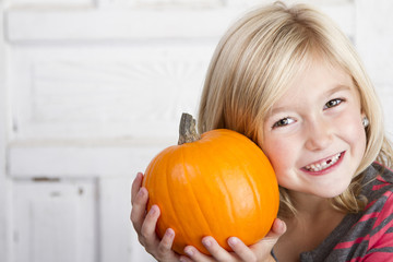 Cute child holding small pumpkin