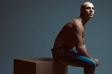 Tough guy concept. Bald muscular male model in blue jeans