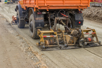 truck compacting gravel at road construction site 2
