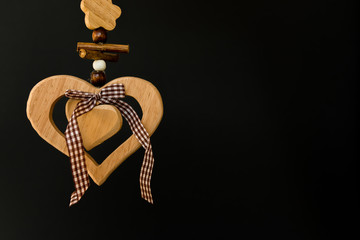 Wooden heart on a rope with wooden balls, a bow in the middle