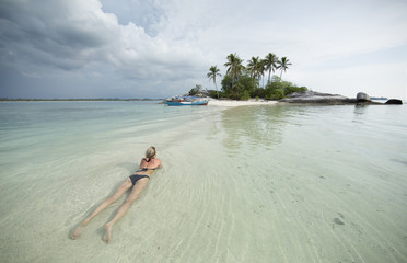 Blonde woman lays in water of ocean, small island and boat