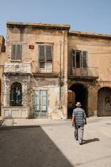 Old Italian man walking among decrepit houses