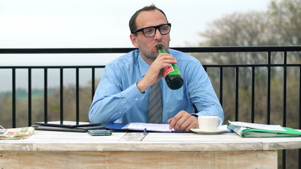 Happy businessman drinking beer, relaxing on terrace