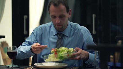 Businessman putting salad on plate during dinner at home
